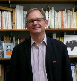 man in glasses in front of bookshelf