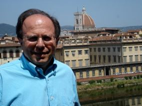 man in blue button down in front of domed building in italy