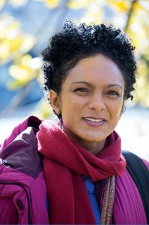 woman in colorful coat and scarf with black curly hair