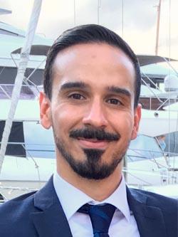 man with dark facial hair smiling softly