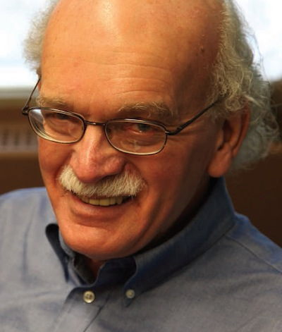 man with glasses wearing blue button down smiling at camera