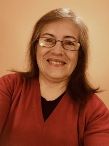 Smiling woman with glasses and shoulder length brown hair
