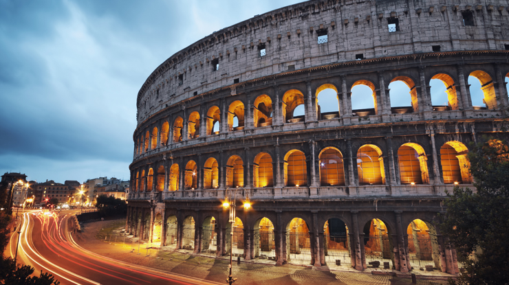 Roman coliseum with streaks of car lights driving below