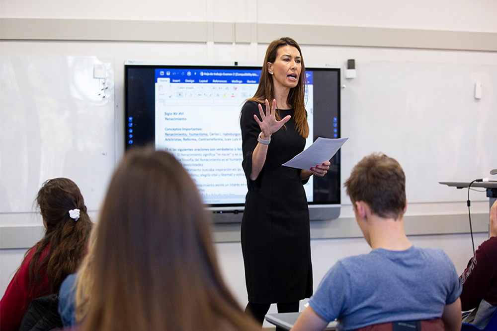 Woman with dark hair lecturing towards a class